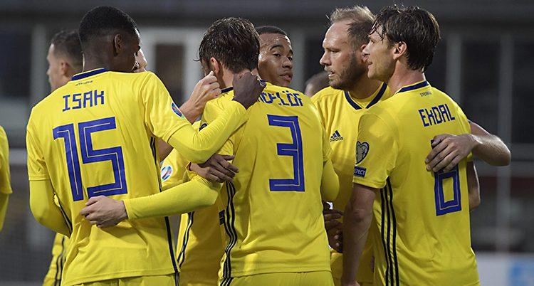 Några spelare i Sveriges landslag i fotboll kramar om varandra efter ett mål. De som står närmast i bilden har ryggen mot kameran. Spelarna har på sig gula tröjor med namn och siffror i blått.