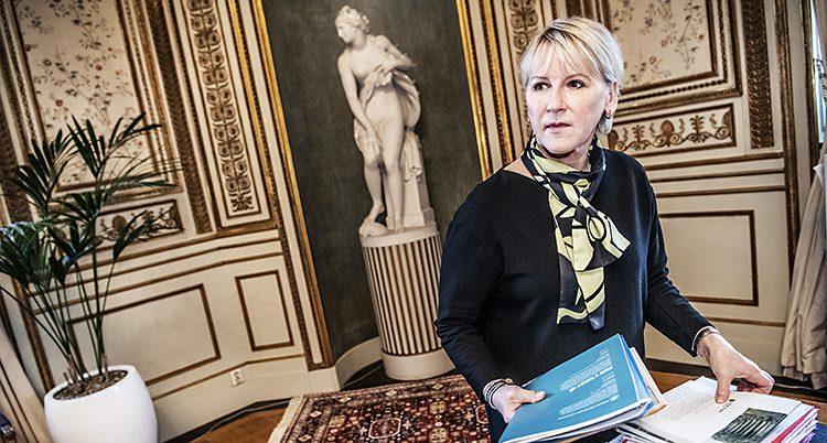 Margot Wallström står vid sitt skrivbord på utrikesdepartementet. Hon fixar med några papper. I bakgrunden syns en staty.