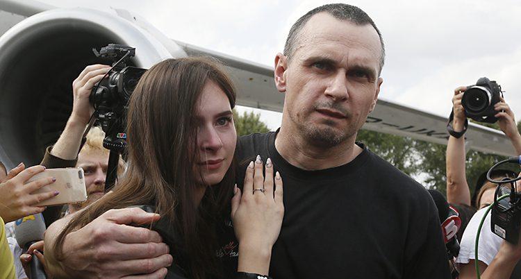 Oleg Sentsov i svart t-shirt håller om sin dotter. Hon ser tårögd ut, han trött.