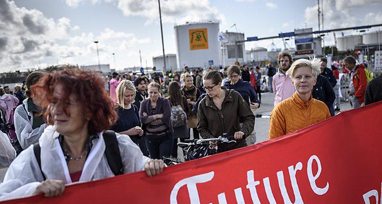 Många människor har samlats i hamnen. Två kvinnor håller i en banderoll med ordet Future i vit text.
