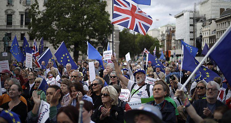 Människor med flaggor från EU och Storbritannien