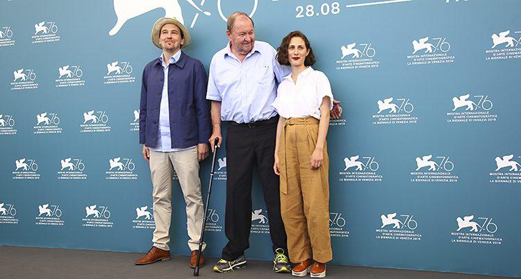De tre står bredvid varandra och ler. På väggen bakom dem är reklam för filmfestivalen i Venedig.