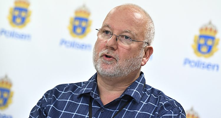 En äldre man med glasögon och vitt skägg framför en vägg med polisernas symbol.