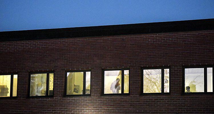 Ett hus av tegel med ljust från fönstren. Himlen är mörk