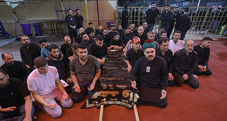 Män på knä i böneposition.