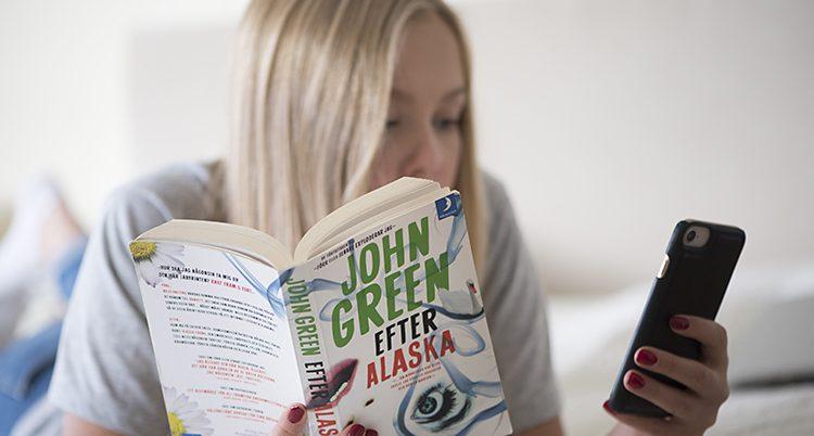 En ung tjej ligger i en säng och kollar på sin mobil. Samtidigt har hon en bok i sin andra hand.