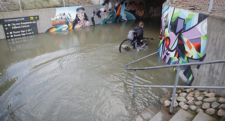 En person bär en cykel genom högt vatten