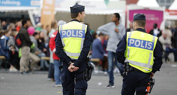 En polis med gul polisväst står på gatan.
