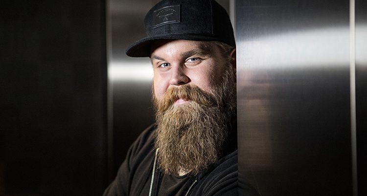 Artisten Chris Kläfford ler mot kameran. Han har ett stort skägg och en svart keps.