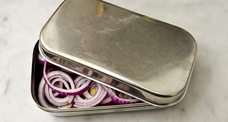 En låda i metall med locket halvt öppet, under syns mat i form av bland annat lök.
