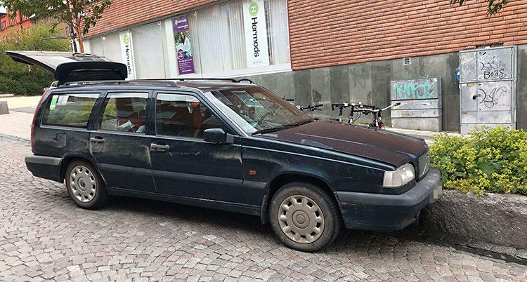 En mörk bil står på en gata med kullerstenar. Det är en mörk Volvo kombi. Bakluckan är öppen. Det är i stadsmiljö, med en liten plantering och ett hus bakom.