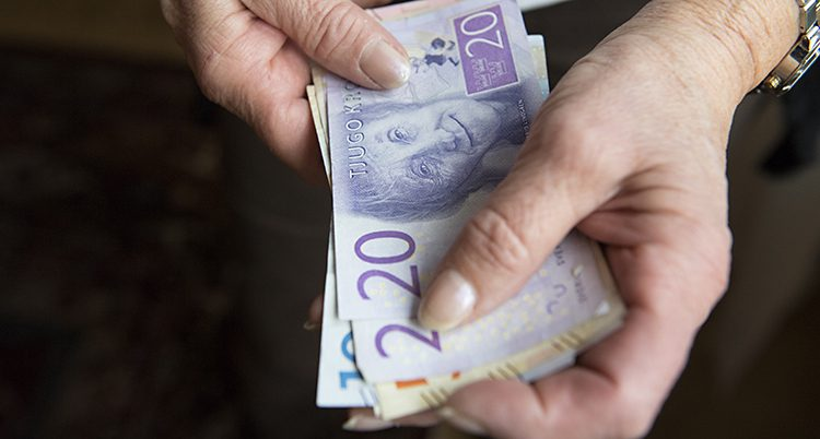 Två rynkiga händer håller i en bunt med sedlar