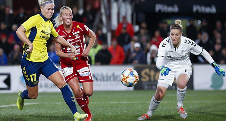 En spelare i gul och blå dräkt jagas av en röd spelare från Piteå och målvakten i vit dräkt.