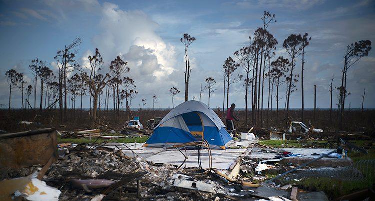 Ett tält står uppställt i ruinerna efter ett hus. En man går bakom