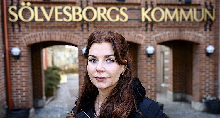 En närbild på hennes när hon står framför kommunhuset i rött tegel