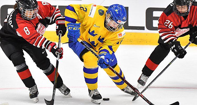 En svensk spelare kämpar om pucken med spelare i röda tröjor.