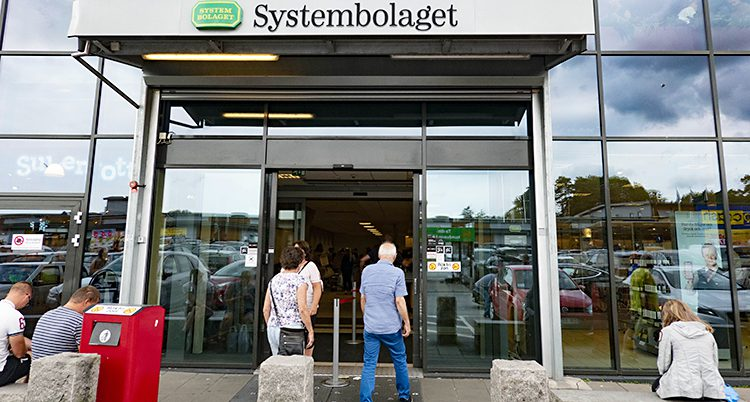 Två personer går in på Systembolaget.
