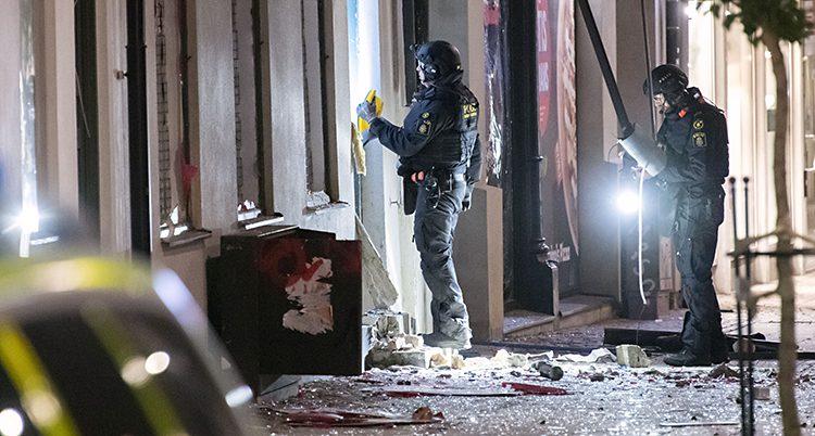 Två poliser med hjälmar och skydd lyser med ficklampor mot marken och ett hus. Det är fullt med krossat glas på gatan.