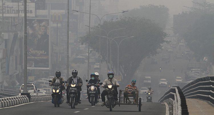 Motorcyklister med munskydd kör på en stor väg. Luften är grå.