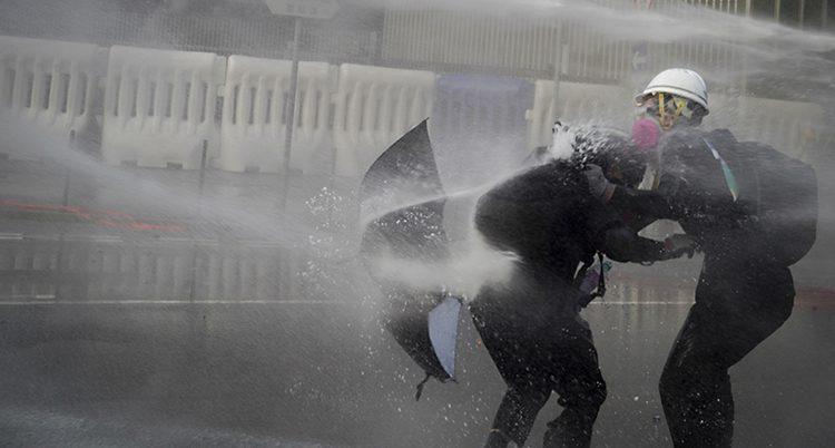 En tjock stråle vatten sprutar mot ett paraply i horisontellt läge. Två personer hukar bakom paraplyet.