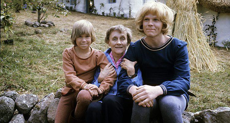 Astrid håller barnen i armkrok, de sitter på en mur