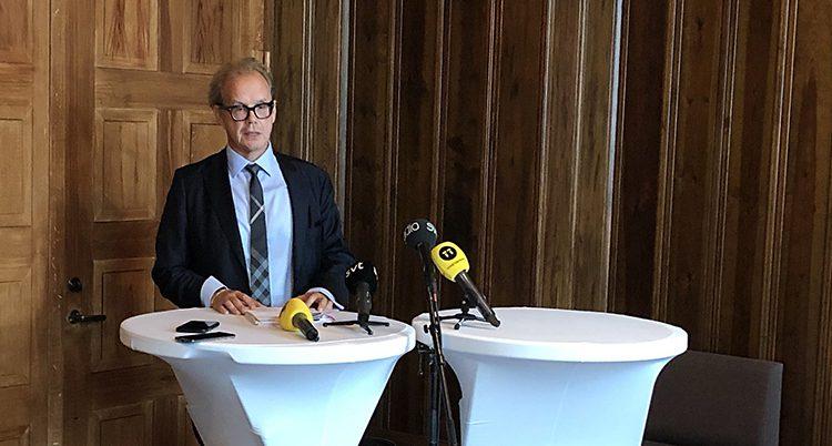 Åklagaren står bakom ett högt bord med mikrofoner framför sig.