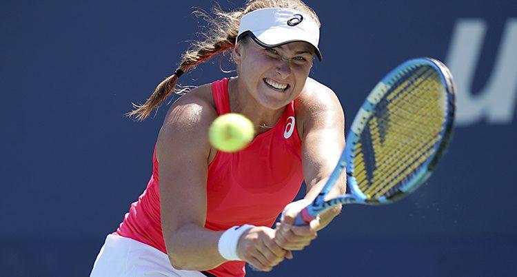 Rebecca Peterson spelar tennis och slår till en boll i en match. Hon har på sig ett orange linne och en vit keps.