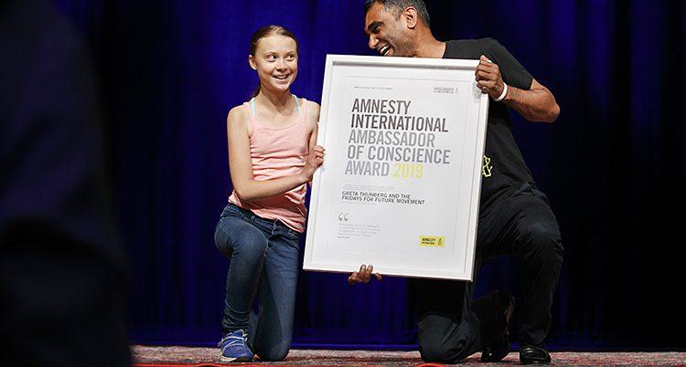 Greta och Kumi på knä bakom en stor tavla med ett diplom.