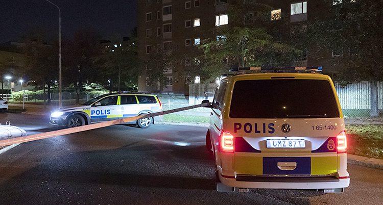 Två polisbilar och en avspärrning framför ett hus. Det är mörkt ute.