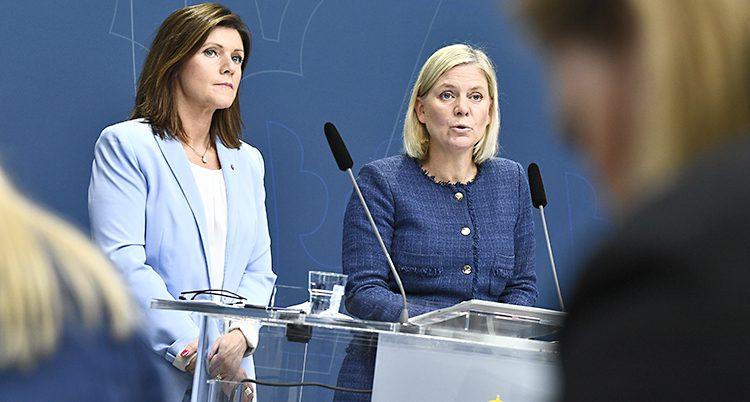 De har blåa kavajer och står bakom ett bord i riksdagen med mikrofoner framför sig