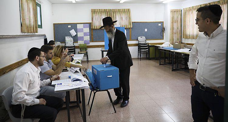 En man med typiskt judiska kläder lägger sin röst i en låda
