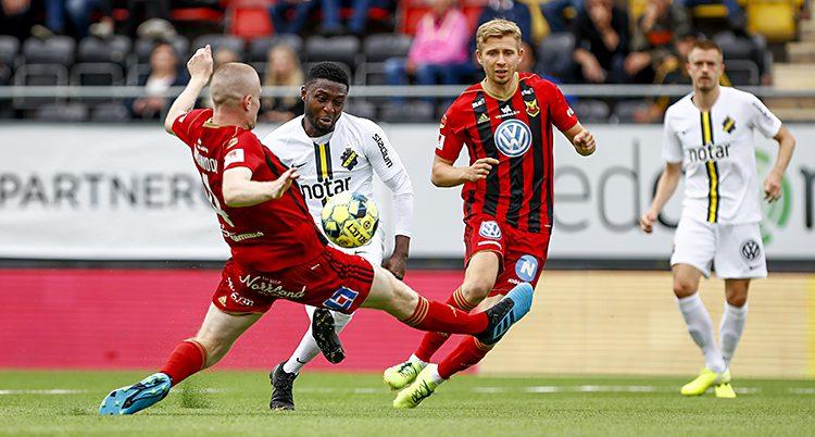 En fotbollsmatch. Fyra spelare syns i bilden. En spelare i rött och en spelare i vitt kämpar om bollen. De andra två spelarna syns i bakgrunden.