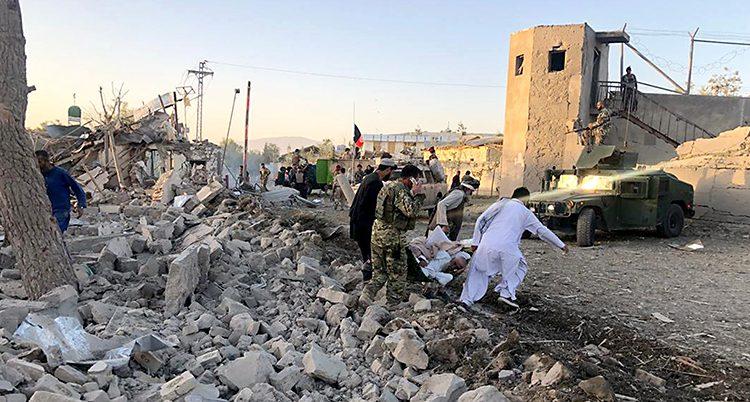 Bilden visar ett hus av sten som har blivit helt förstört. En massa stenar ligger på marken. Några personer lyfter bort en skadad människa.
