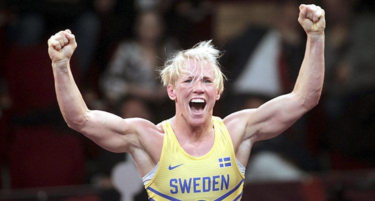 Brottaren Jenny Fransson sträcker armarna i luften efter att hon vunnit en match. Hon skriker ut sin glädje. Hon har blont hår och ett gult linne som det står Sweden på, i blått.