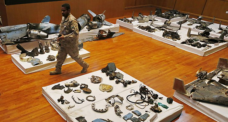 En militär går bland prylar som logger på vida dular på golvet. Det är metalldelar som ska vara delar av vapen.