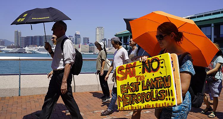 Människor går längs havet, med paraplyer som skydd för solen.