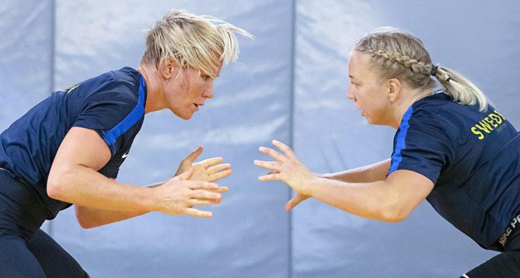 Två kvinnor som tränar brottning. De står framför varandra och håller ut armarna. De ser beredda ut. Båda har blont hår och tröjor som det står Sweden på.