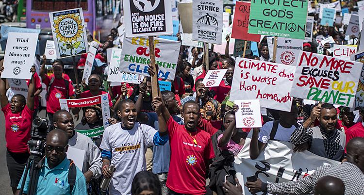 Många unga personer trängs, ropar och håller upp skyltar med budskap på engelska om klimatet.