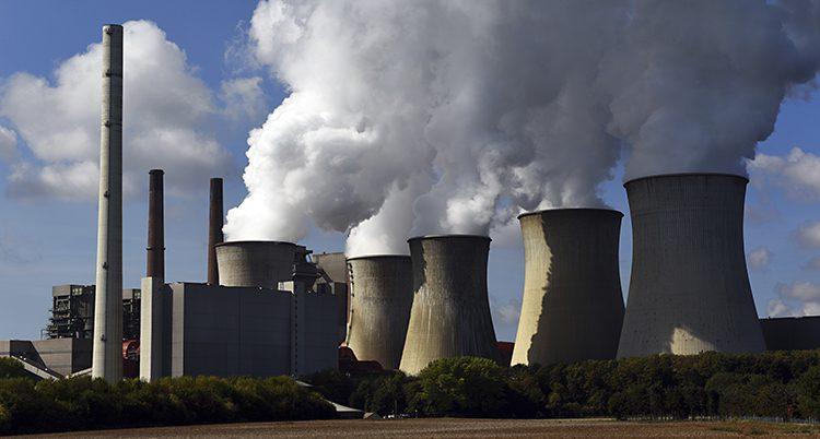 En stor fabrik med flera stora skorstenar. Det kommer mycket rök ur skorstenarna. Röken går upp i en blå himmel där det finns några moln.
