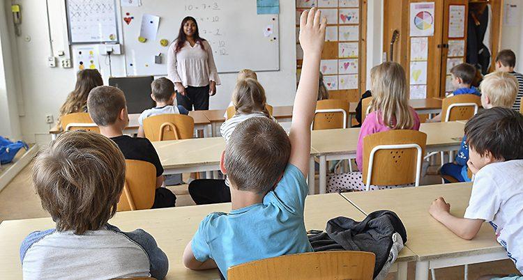 Elever räcker upp handen i ett klassrum.