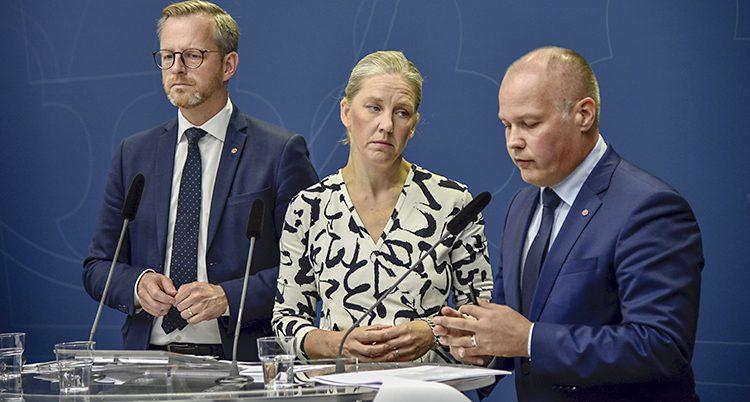 De tre ministrarna står på rad famför ett bord. Morgan Johansson talar.