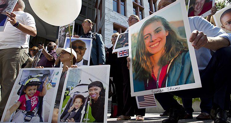 Människor med stora skyltar. På skyltarna är bilder av anhöriga som dött.