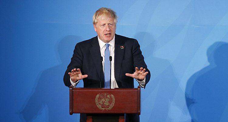 Boris Johnson står och håller ett tal. Han står vid en röd pulpet med FN:s symbol på och pratar i en mikrofon. Han har en mörk kostym, vit skjorta och blå slips. Väggen bakom är blå.