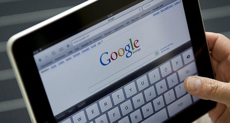 En hand håller i en surfplatta med sidan Google öppen