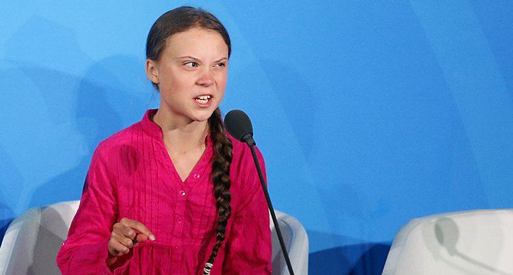 Greta har en rosa skjorta och ser arg ut i ansiktet, hon pekar med ena handen