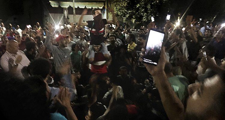 Kväll i Kairo, folk trängs och ser ut att ropa saker, någon håller upp en mobiltelefon.