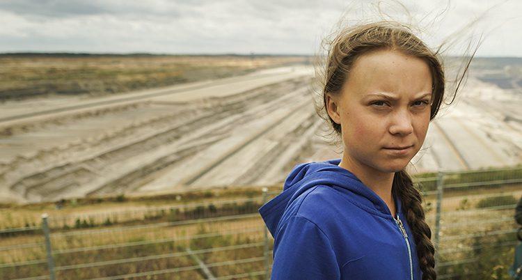 Greta Thunberg tittar in i kameran. Hennes hår blåser lite i vinden. Hon har en fläta och en blå tröja. I bakgrunden syns ett stort fält.
