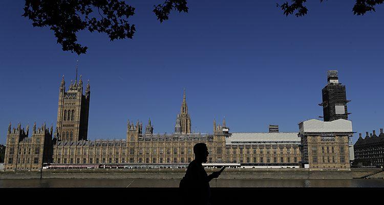 En bild av ett stort och gammalt hus i London. Det är riksdagen i Storbritannien. Bilden är tagen på ett ganska långt avstånd. En fotgängare går förbi i förgrunden och några trädgrenar hänger ner i ovansidan av bilden.