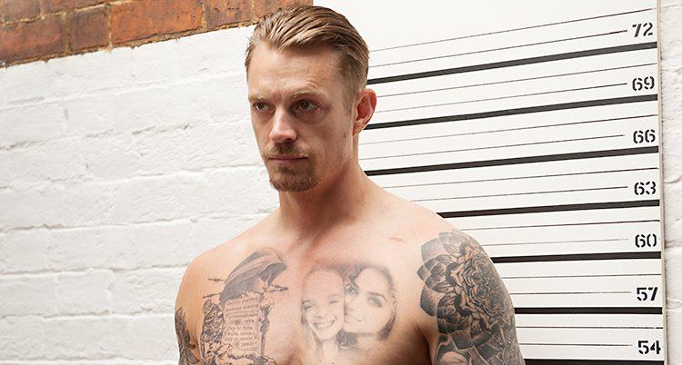 Kinnaman står med bar överkropp full med tatueringar.