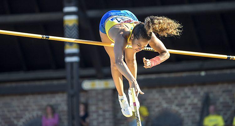 En kvinna som hoppar stavhopp. Hon ligger i luften över ribban och är precis på väg att släppa staven.